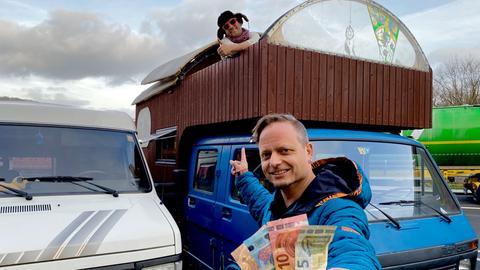 Friso Richter steht mit Euroscheinen in der Hand vor einem umgebauten Campingvan. Aus dem ausgebauten Dach schaut ein Mann heraus und zeigt den ausgestreckten Daumen.