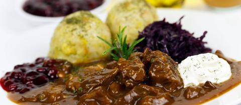 Gulasch, Knödel und Rotkohl auf einem Teller.