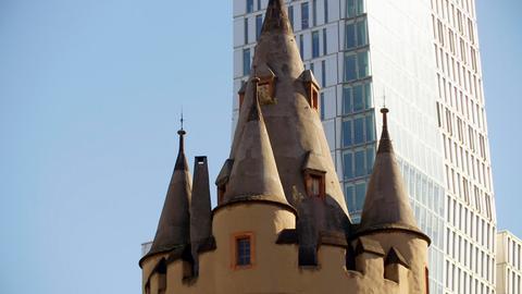 """Blick auf die Spitze des Eschenheimer Turms; im Hintergrund der neu erbaute """"Nextower"""" mit seiner Glasfassade."""