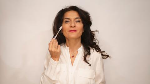 Sevgi Schäfer schminkt eine Frau.