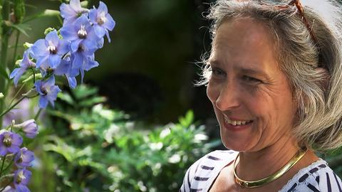 Eine Frau freut sich über ihren Garten.