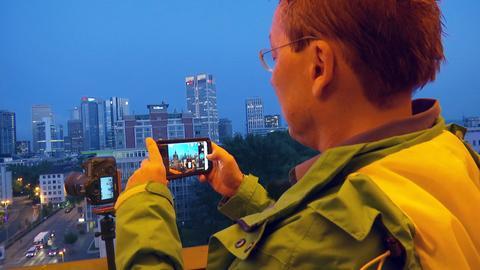 Influencer Paul Dylla fotografiert für Instagram die Skyline von Frankurt.