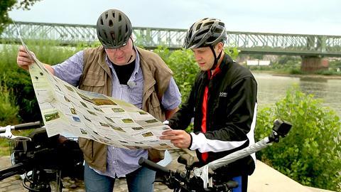Radfahrer studieren eine Radfahrkarte am Main