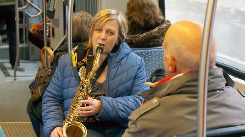 Eine Frau spielt Saxophon in der Bahn.