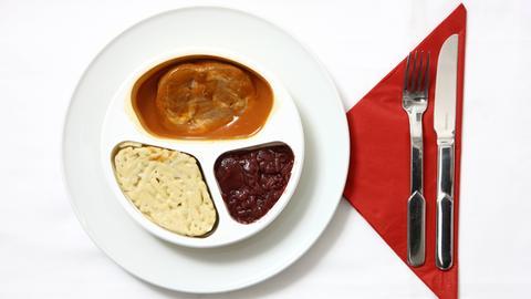 Fertiggericht in der Originalverpackung, angerichtet auf einem Teller: Schweinebraten mit Spätzle und Apfelrotkohl.