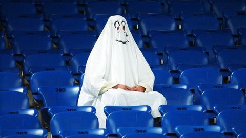 Ein, als Geist verkleideter, Mensch sitzt auf einer ansonsten leeren Zuschauertribüne.