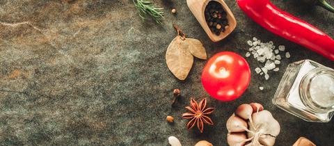 Zutaten für eine Tomatensauße und Sternanis auf einem Brett