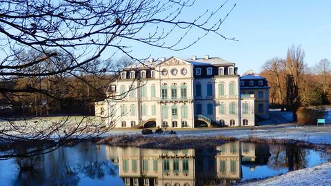 Ein Schloss vor einem See mit vereisten Grünflächen.