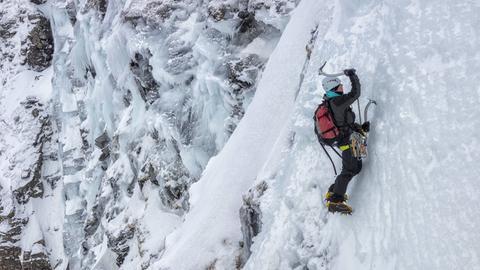 Ein Mensch hängt an einer zugefrorenen Bergwand.
