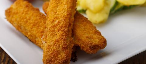 Fischstäbchen mit Kartoffelsalat auf dem Teller