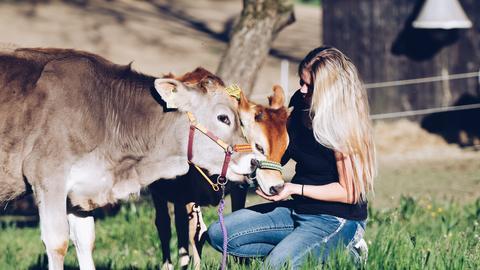 Lena Mader schmust mit Kuh und Kälbchen auf einer Weide.