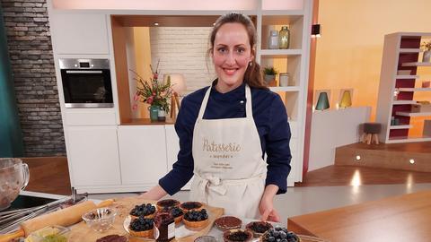 Konditormeisterin Theresa Mendel im hallo hessen-Studio mit vielen Heidelbeer-Tartelettes.