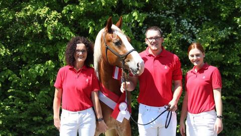 Felix Hoffarth posiert mit einer jüngeren und einer älteren Frau und einem Pferd mit Auszeichnung.