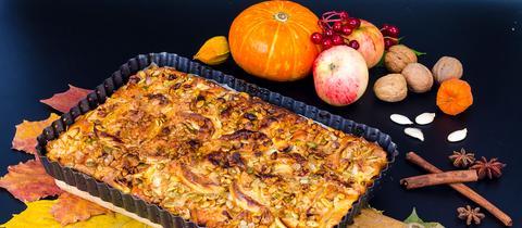 Ein Apfel-Kürbiskuchen auf herbstlicher Deko.