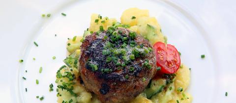 Frikadelle auf Kartoffelsalat mit Schnittlauch.