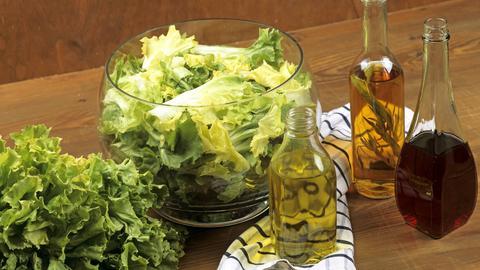 Endiviensalat wird mit Öl und Essig verfeinert