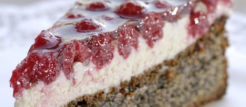 Mohn-Himbeer-Torte, Tortenstück im Vordergrund und angeschnittene Torte im Hintergrund unscharf.