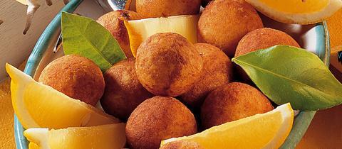 Fischbällchen garniert mit Zitronenschnitzen und Basilikumblättern in einer mediterranen Schüssel.