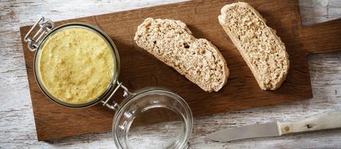 Linsenaufstrich in einem Glas und Brot auf einem Brett.