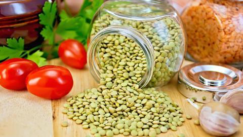 Grüne Linsen, die aus einem Glasbehälter gekippt sind. Mit Tomaten und Knoblauch, im Hintergrund steht ein verschlossener Glasbehälter mit roten Linsen.