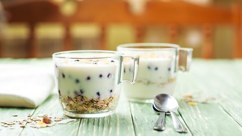 Ein Joghurt-Desser im Glas mit Beeren und Haferflocken.