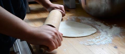 Eine junge Frau rollt einen Teig mit einem Nudelholz aus.