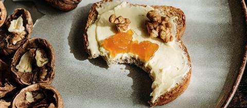 Ein Toast mit Walnussbutter und etwas Marmelade auf einem Teller, daneben Walnüsse.