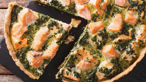 Angeschnittene Pie beziehungsweise Quiche mit Lachs und Spinat auf schwarzer Schieferplatte.