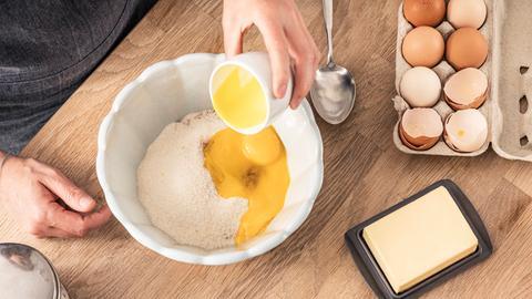 Eine Frau gibt Eier in eine Teigschüssel. Auf der Arbeitsplatte liegen außerdem Butter, eine Eierpackung und weitere Zutaten.