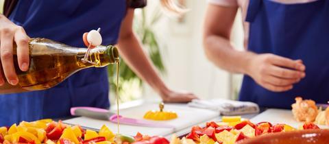Eine Person beträufelt Paprika auf einem Blech mit Olivenöl.