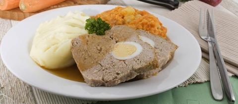 """Zwei Stücke """"Falscher Hase"""" mit Kartoffelstampf und Karrottenpüree auf einem Teller. Im Hintergrund rohe Möhren und zwei Zwiebeln."""