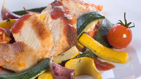 Aufgeschnittene Hähnchenbrust mit Zucchini, Tomate und Knoblauch.