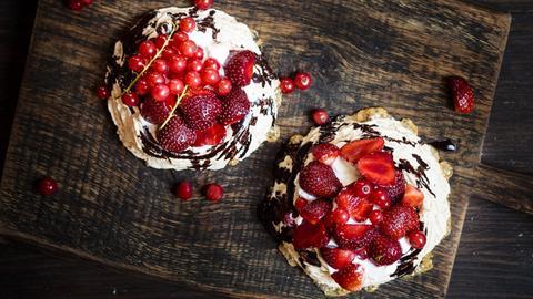 Johannissbeer-Erdbeer-Törtchen auf einem Brettchen.