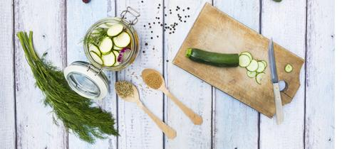 Zucchinis im Einmachglas mit Gewürzen und Kräutern.