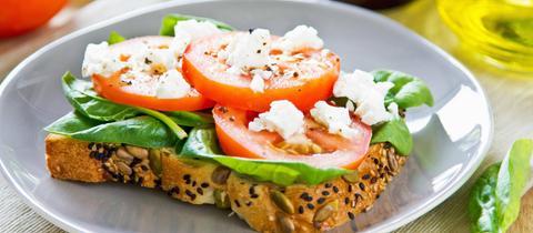 Spinat, Feta und Tomate auf einer Brotscheibe.