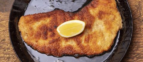 Ein gebackenes Schnitzel mit Zitrone in einer Pfanne.