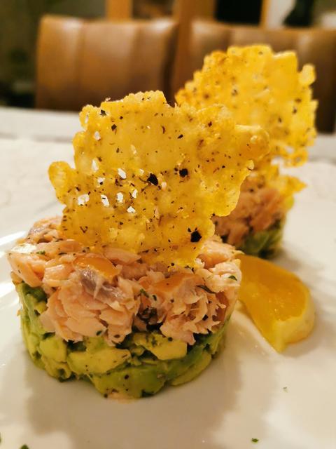 Zwei Bärlauch Avocado Lachs Türmchen mit Parmesan Bärlauch Cracker und eine halbe Zitronenscheibe auf einem weißen Teller angerichtet.