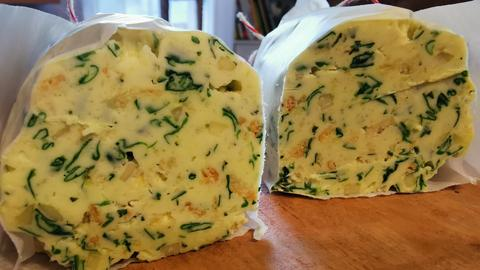 Zwei angeschnittene Rollen der Crunchy Bärlauch Butter.