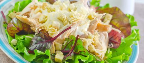 Teller mit grünem Salat und Dressing