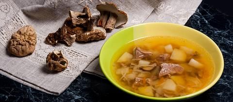 Ein Teller Suppe und Steinpilze auf einer Tischdecke