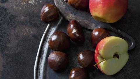 Maronen und Äpfel mit einem Messer