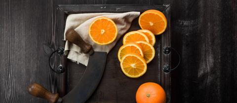 Orangen und Orangenscheiben mit Messer auf einem Brett.