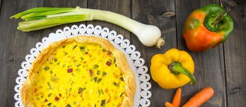 Eine gebackene Quiche mit Paprikas und Lauch auf dem Tisch.