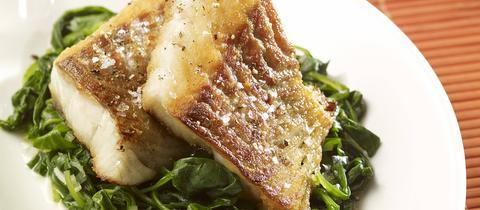 Seelachsfilet mit Spinat auf einem Teller.