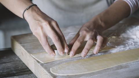 Eine Frau sticht ausgerollten Teig aus.