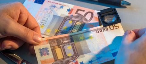 Gefälschte Euro-Geldscheine unter einer Lupe.