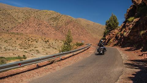 Ein Motorrad fährt auf einer Strasse die durch eine Landschaft im Hohen Atlas westlich des Toubkal in Marokko.