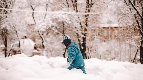 Ein Kind spielt im Schnee