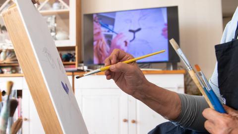 """Eine Frau sitzt in ihrem Wohnzimmer an einer Staffelei, während auf dem Fernseher ein Online-Malkurs des Berliner Start-ups """"ArtNight"""" läuft."""