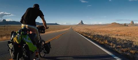 Mann auf Fahrrad in amerikanischer Wüste